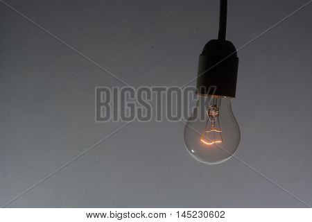 incandescent light bulb turned on at low power in low key