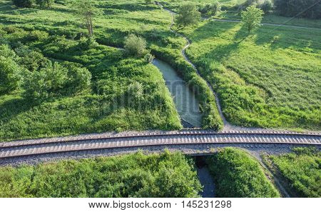 Aerial view of the village railway going across the bridge over boggy creek and paths through the green vegetation.