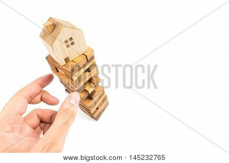Hand picking up building block with House on top. House construction concept.Business risk concept
