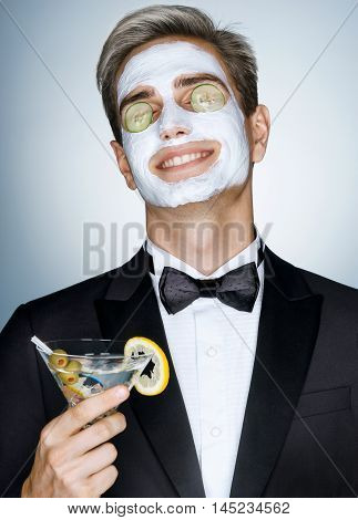 Good skin care is very important. Happy gentleman receiving spa facial treatment. Photo of Handsome man with a facial mask on his face and cucumber on his eyes
