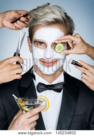 Beautiful man with moisturizing facial mask surrounded by the different service hands (stylist beautician hairdresser). Photo of happy stylish man receives the spa treatments. Grooming himself