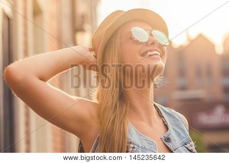 Portrait of beautiful stylish young girl in casual clothes hat and sun glasses looking at the sun and smiling while walking outdoors