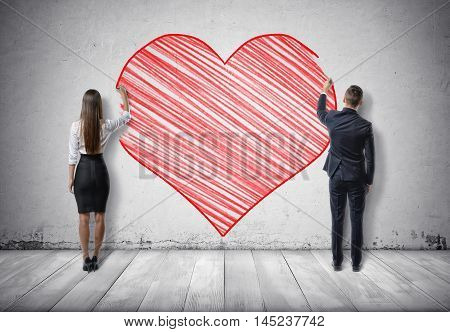 Back view of a businessman and a businesswoman drawing big red heart on concrete wall. Office romance. St Valentine's day. Love and tenderness.