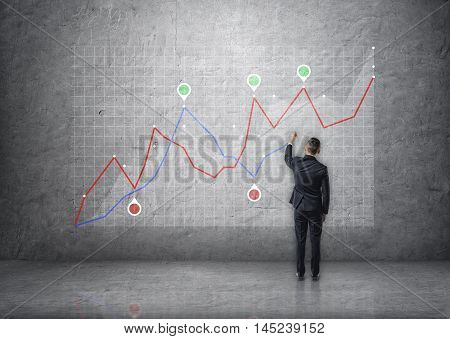Back view of a businessman drawing rising graph on concrete wall. Chart growth concept. Successful investment. Profit and benefit.