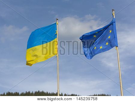 Flags of Ukraine and the European Union are developing on the background of the sky