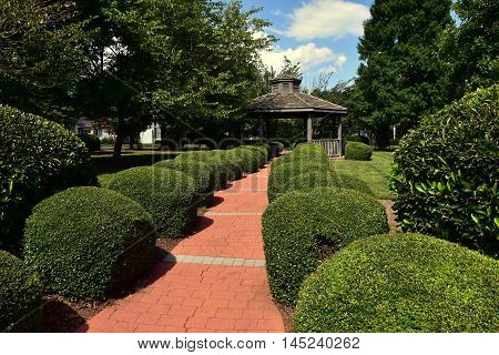 Pittsboro North Carolina - July 29 2016: Brick pathway lined with clipped shrubbery leads to a wooden gabebo at Fearrington Village