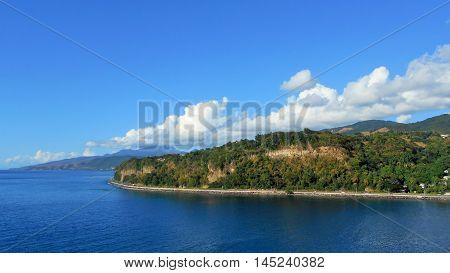 Caribbean coastal highway blue ocean distant cliff puffy white cloud