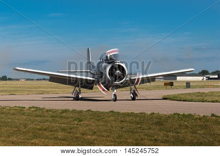 EDEN PRAIRIE MN - JULY 16 2016: AT-6 Texan airplane makes a turn on the taxiway after landing at air show. The AT-6 Texan was primarily used as trainer aircraft during and after World War II.