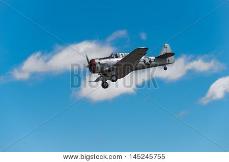 EDEN PRAIRIE MN - JULY 16 2016: AT-6 Texan airplane comes in for a landing against cloudy sky at air show. The AT-6 Texan was primarily used as trainer aircraft during and after World War II.