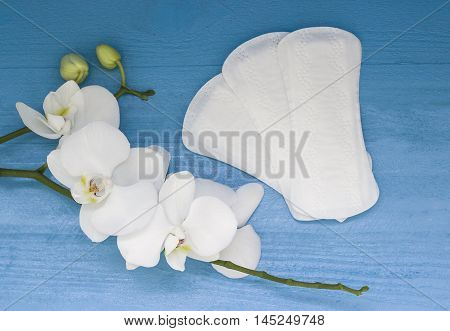 Sanitary pads and lilac orchid on the blue wooden background