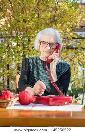 Elderly Woman Using Phone In The Backyard