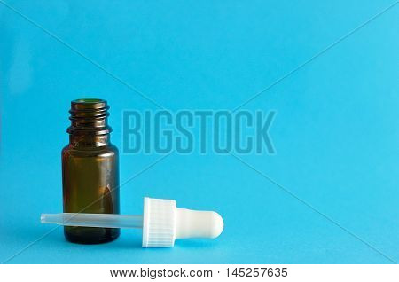 A brown bottle with a dropper isolated on a blue background
