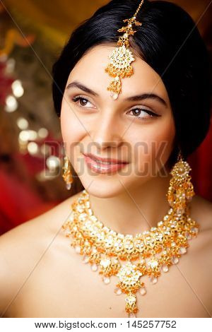 beauty sweet real indian girl in sari smiling on black background, jewelry shining
