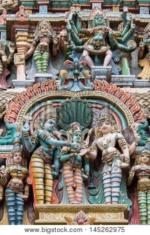 Madurai India - October 19 2013: Closeup of the wedding scene of Meenakshi and Shiva while Vishnu gives his sister away. Facade of West Gopuram at Meenakshi Temple. Devi Kali and other statues in photo.