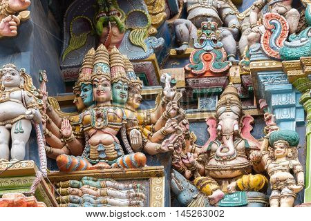 Madurai India - October 19 2013: Closeup of goddess Gayatri sitting on coffin with the four Vedas inside. Ganesha keeps her company. Facade of West Gopuram at Meenakshi Temple.