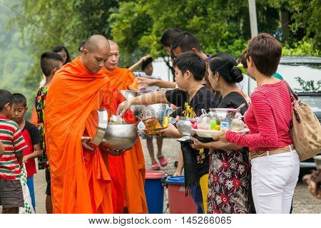 Sangkla Buri Kanchanaburi THAILAND - OCT 26 : Buddhist monks are given food offering from people for End of Buddhist Lent Day. on October 26 2013 in Sangkla BuriKanchanaburiThailand.