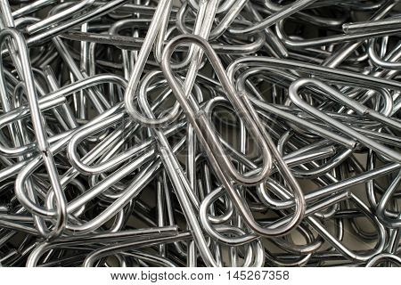 An extreme close up image of metal paper clips