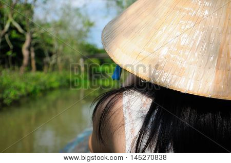 An asian woman smiling wearing a traditional vietnamese hat (nong la) on a wooden boat within the Mekong River Delta in south vietnam.