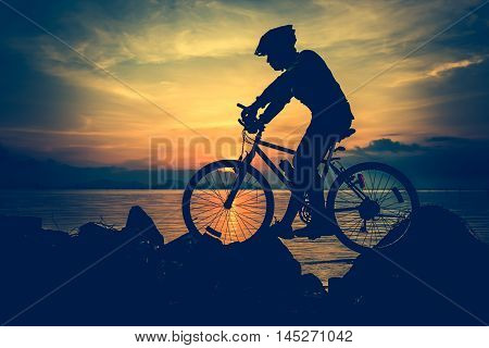Silhouette of bicyclist riding the bike on a rocky trail at seaside on colorful sunset sky background. Active outdoors lifestyle for healthy concept. Vintage style. Cross process.