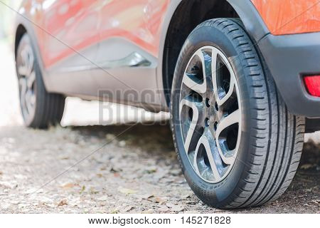 Close up of car tyres. Back view of a parked car over a road covered with autumn leaves.