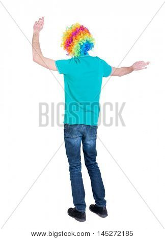 back view of dancing young beautiful man in clown wig. Curly man in a turquoise sweater and clown wig emotionally gesticulates.