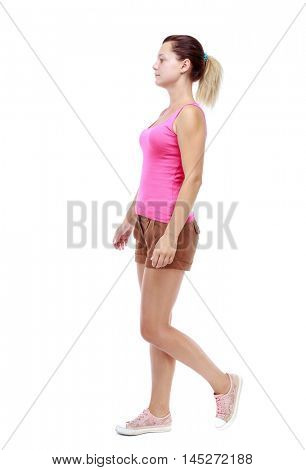 back view of walking woman. beautiful girl in motion. Isolated over white background. Sport blond in brown shorts out sideways.