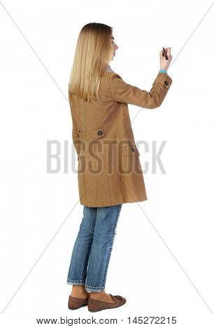 back view of writing beautiful woman. blonde in a brown coat paints a felt-tip pen plan