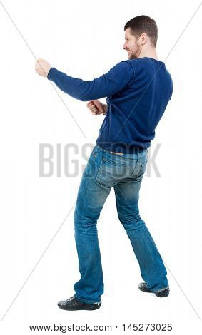 back view of standing man pulling a rope from the top or cling to something. bearded man in blue pullover pulls the rope side.