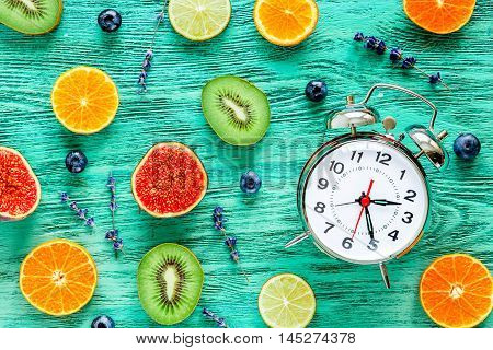 alarm clock - time to wake up with fruits on green wooden table