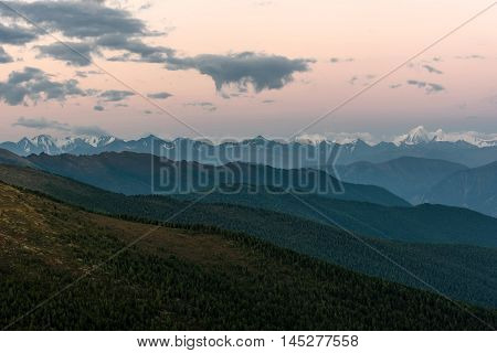Scenic view of the beautiful mountain peaks with snow contours of mountains slopes covered with forest and pink sky at sunrise