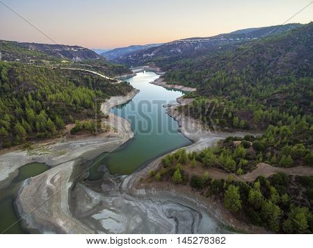 Aerial view of Diarizos river at sunset in Paphos Cyprus. The river cutting through the green valley and lush forest of laona mountain leading to the Venetian bridge from the Arminou reservoir.