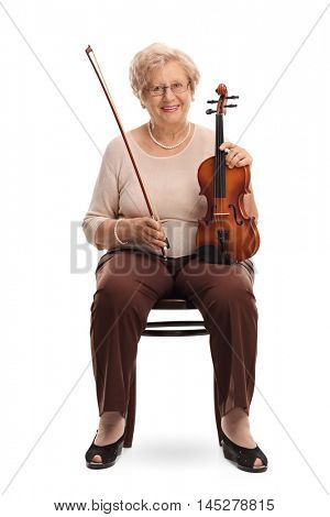 Mature woman seated on a chair holding a violin and a bow isolated on white background