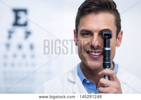 Close-up of smiling optometrist looking through ophthalmoscope in ophthalmology clinic