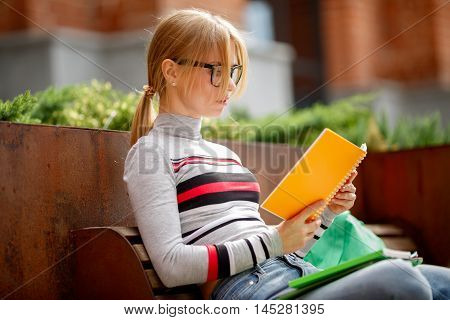 girl in glasses with notebooks in their hands sitting on bench in afternoon