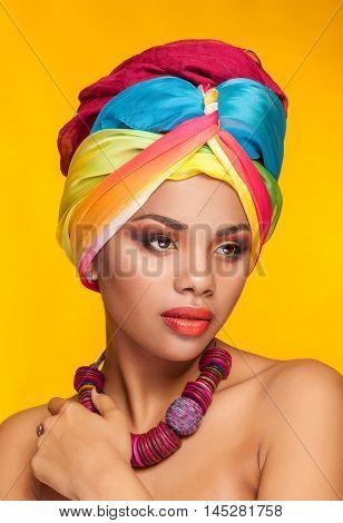 Afro American Girl Wearing An Ethnic Turban On Yellow Background