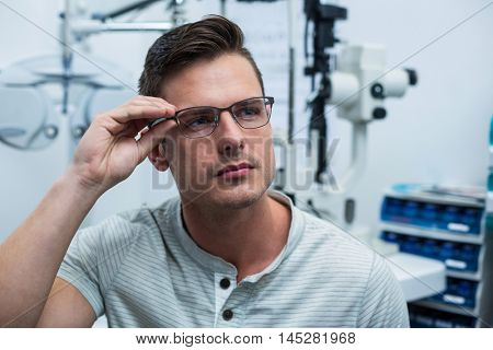Close-up of handsome patient trying spectacles in ophthalmology clinic