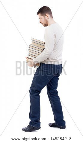 A man carries a heavy pile of books. back view. bearded man in a white warm sweater, tries to comfortably grasp the stack of books.