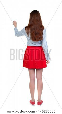 back view of writing beautiful woman. Long-haired brunette in red skirt draws a felt-tip pen on the wall.
