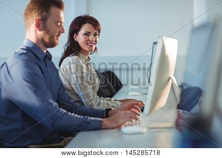 Portrait of mature students using computer in the computer room at college