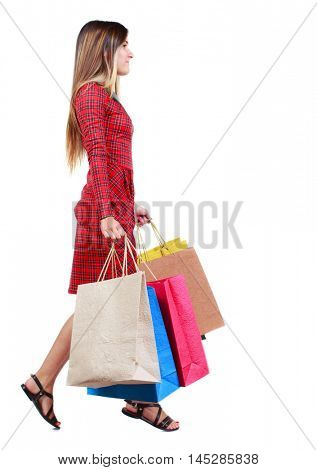 side view of going woman with shopping bags . beautiful girl in motion. backside view of person. girl in red plaid dress runs in the side with colorful paper bags in their hands.