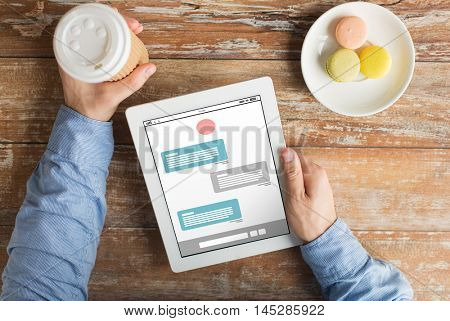 business, online communication, people and technology concept - close up of male hands with messenger on tablet pc computer screen, cookies and coffee cup on wooden table