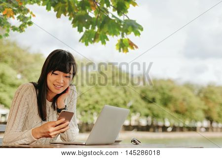 Smiling Young Woman Using Mobile Phone At Outdoor Cafe.