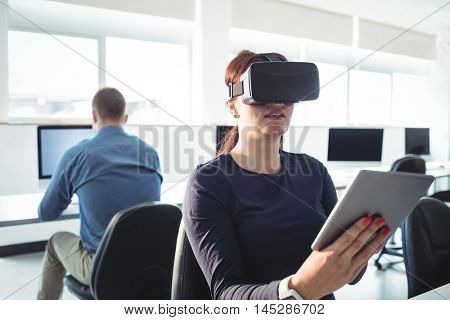 Mature student in virtual reality headset using digital tablet to help with studying at college