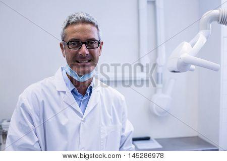 Portrait of a dentist adjusting light in dental clinic