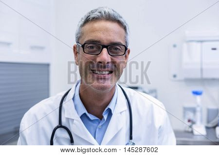 Portrait of dentist in spectacles at dental clinic