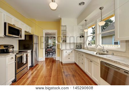 Kitchen Interior With White Cabinets, Yellow Walls And Wood Floor