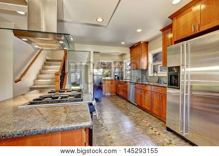 Kitchen Interior With Tile Flooring And Brown Cabinets
