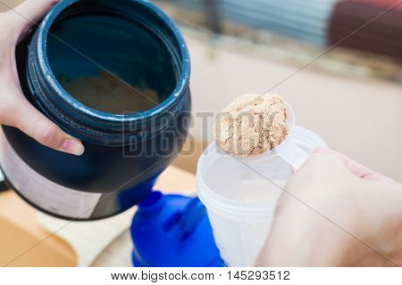 Scoop of whey protein on a wooden plate with jar.
