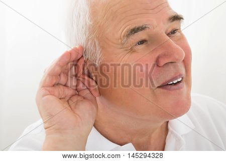Senior Man Trying To Hear With Hand Over Ear