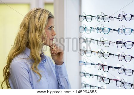 Thoughtful female customer selecting spectacles in optical store